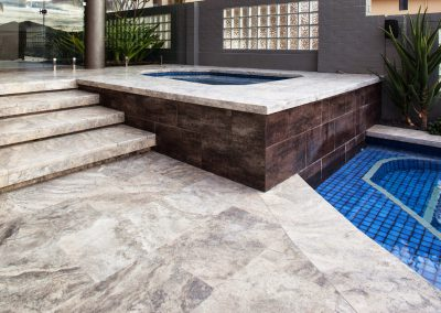 silver travertine unfilled and tumbled pool coping and pavers outdoors spa