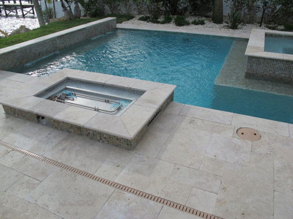 ivory pool coping tiles unfilled and tumbled around pool