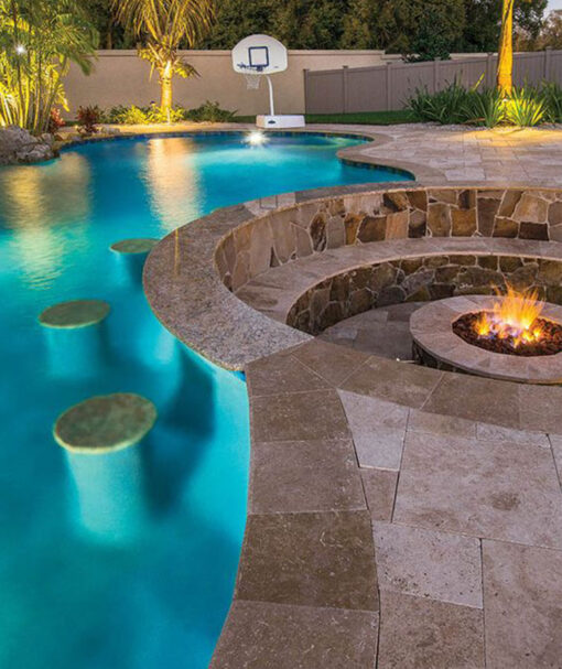 Travertine tiles around a fire pit and pool.