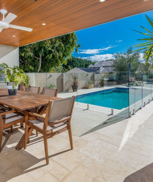 Ivory travertine tiles around a pool with an outdoor table.