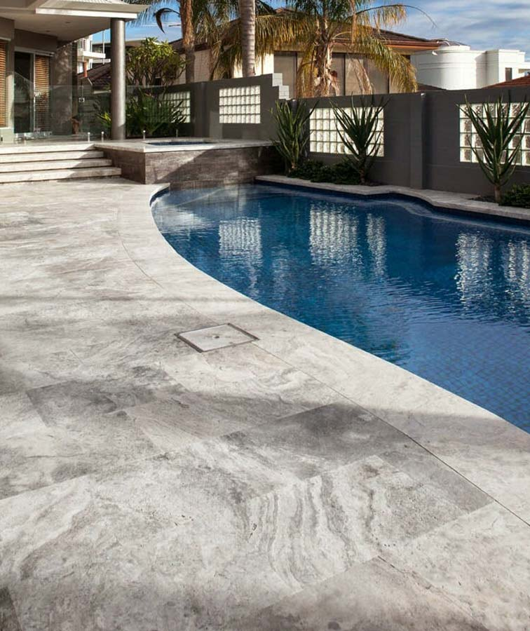 French pattern silver travertine tiles around a pool area.