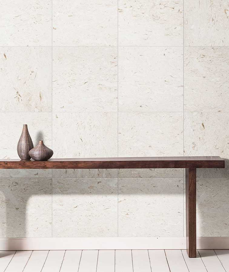 Shell white tiles used as across a wall with a wooden bench.