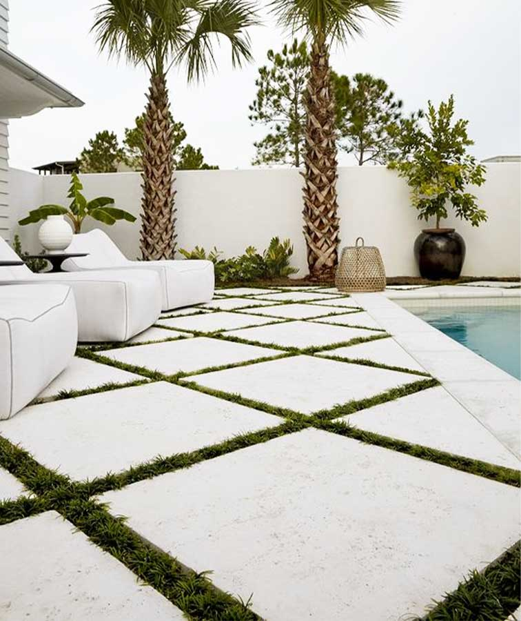 White Limestone pavers laid outside in between grass.
