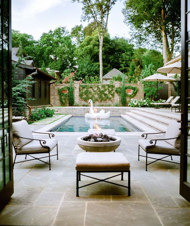 Outdoor tiles, outdoor firepit and a swimming pool with a swan.