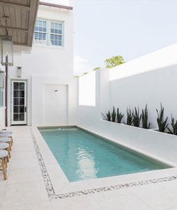 White travertine tiles and pool coping around a pool area.
