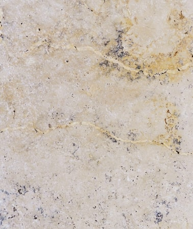 Antique travertine paver with yellow patterns.