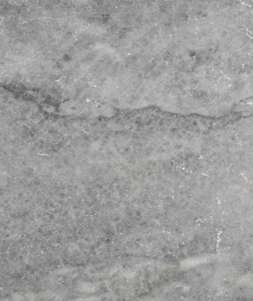 The surface of a grey limestone tile.