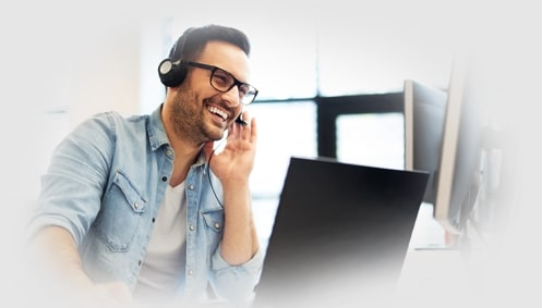Smiling man talking on a headset using a laptop.
