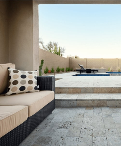 Travertine tiles around a pool area with an outdoor couch.