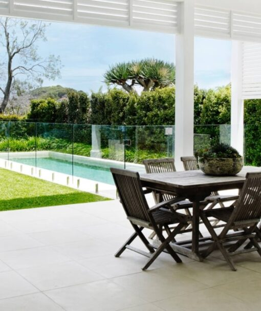 White outdoor pavers with a black outdoor table set.