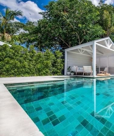 White pool coping tiles around an aqua pool.